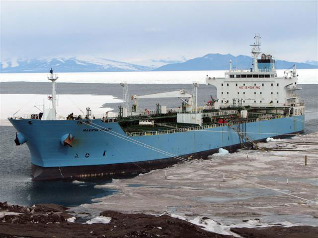 Large ship docks near slushy ice.