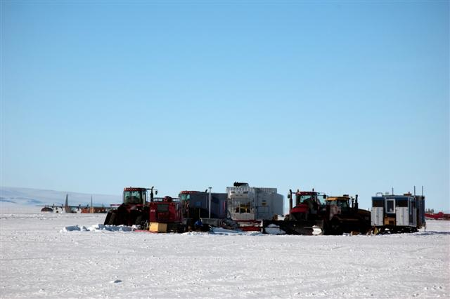 Tractors and buildings on ice with planes in background.