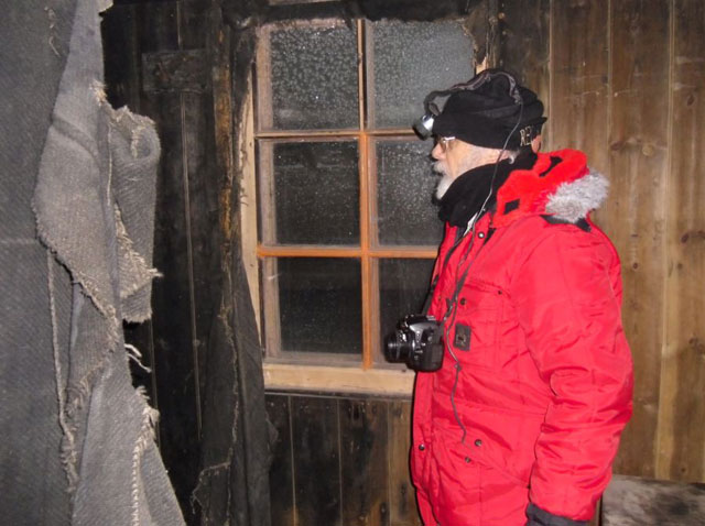 Person with headlamp inside wood building.
