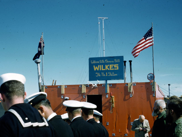 Men in naval uniforms stand near a building.