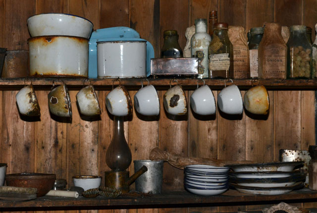 Old dishware hangs from a shelf.