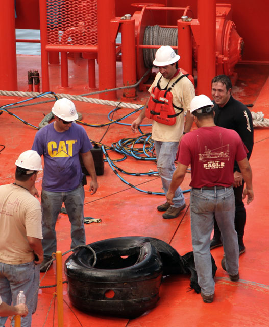 People surround tire on ship deck.