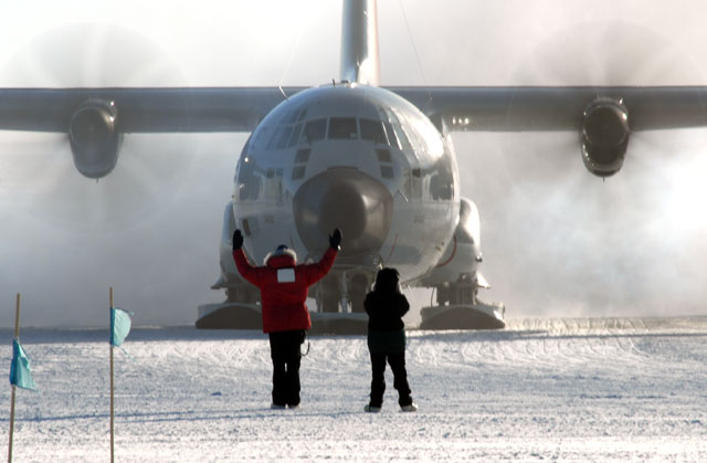 People direct an airplane on ice.