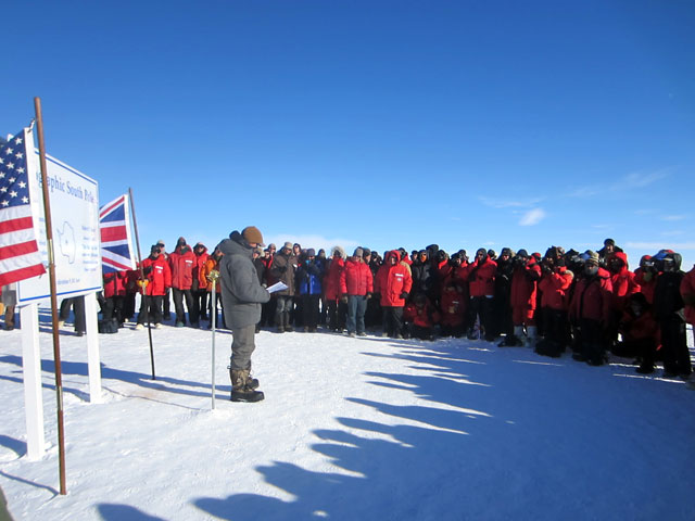 Crowd gathered around geographic South Pole and speaker.