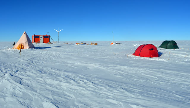 Tents and orange building on snow.