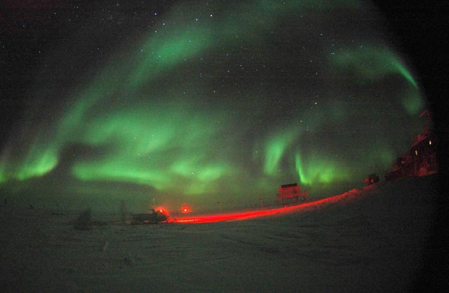 Auroras illuminate night sky.