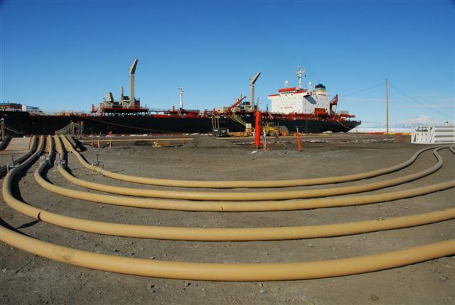 Lines of hose laid out in front of ship.