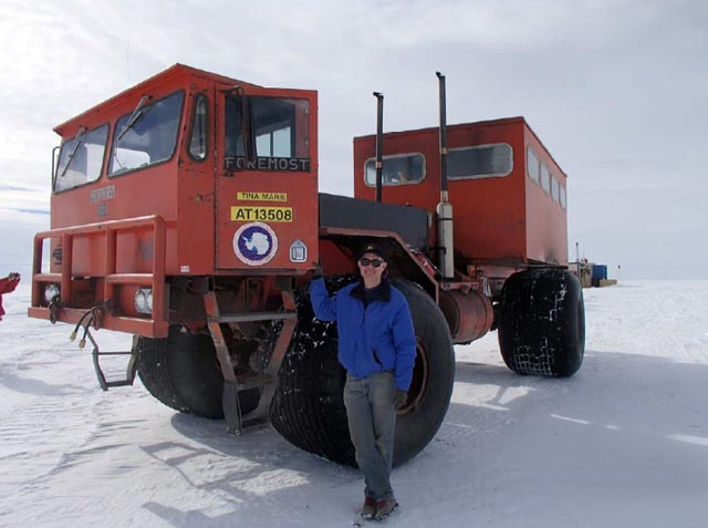 Man stands next to large vehicle.