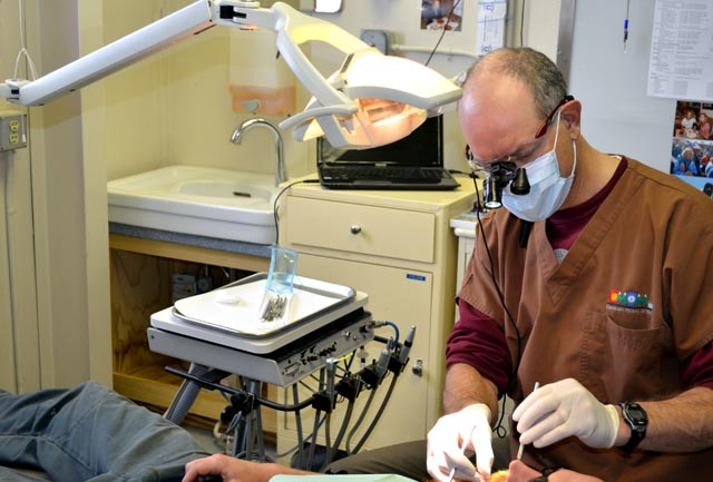 Dentist performs dental work.