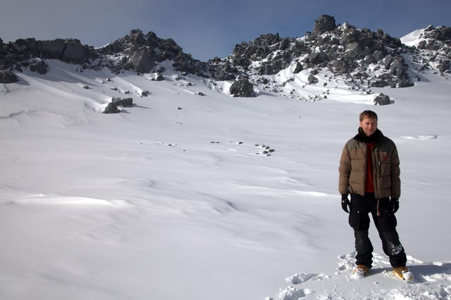 Person stands in snowy, rocky landscape.