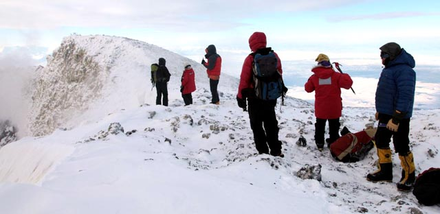 People stand on snowy ridge.
