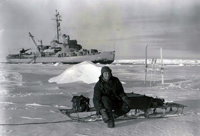 Man sits on ice with ship in background.