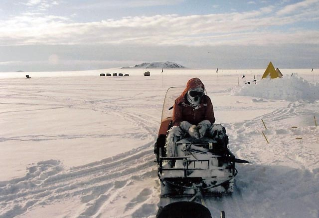 Person sits on snowmobile in snowy place.