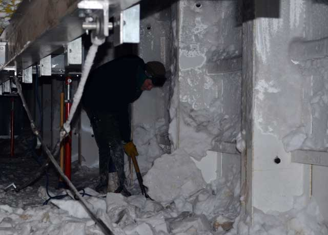 Person shovels ice from underneath a building.