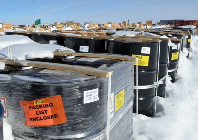 Barrels and other items covered by snow outside.