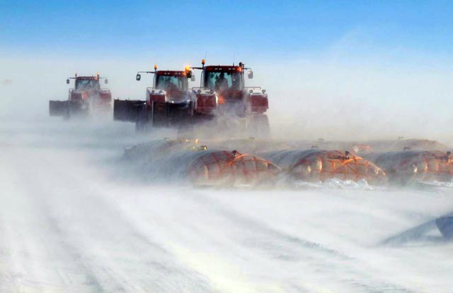 Snow blows around a line of tractors and bladders.