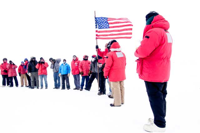 People stand in line around flag.