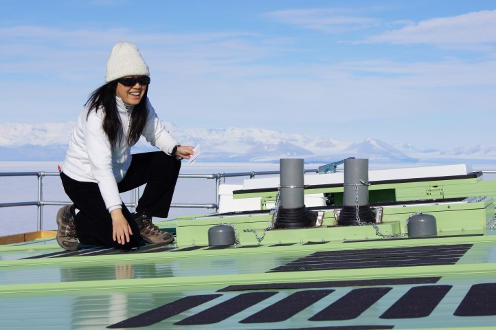 Woman kneels on roof of green building.