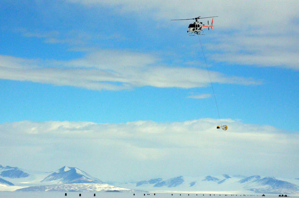 Helicopter flies instrument over ice.