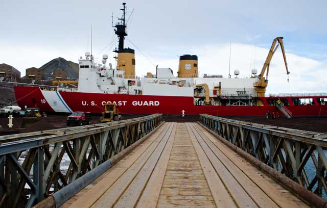 View of ship across wooden bridge.