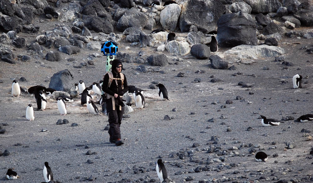 Person walks through rocky area with backpack instrument.