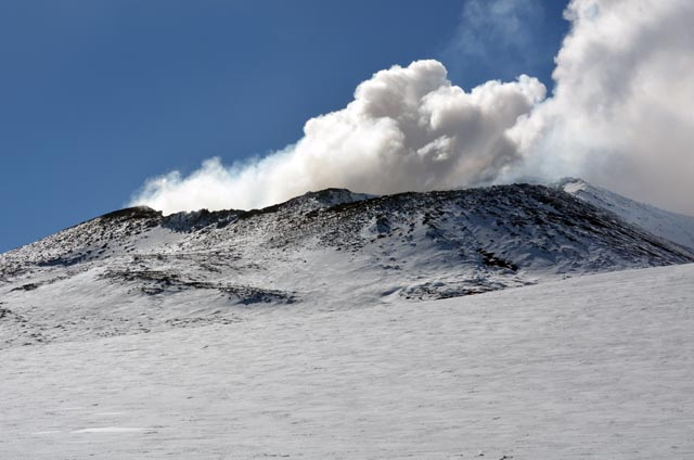 Smoke emerges from cone of volcano.