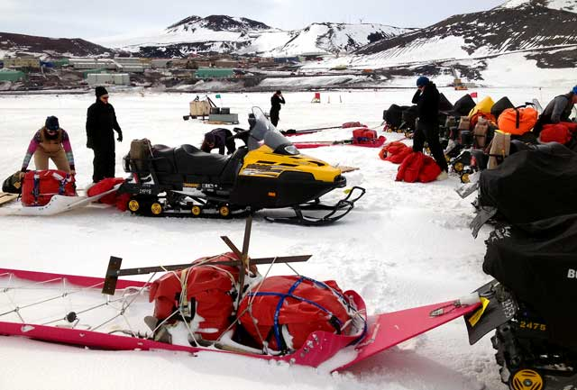 People load sleds for snowmobiles.