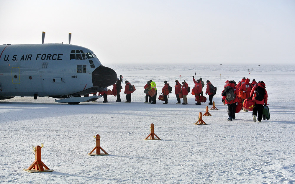 People board an airplane in cold weather.