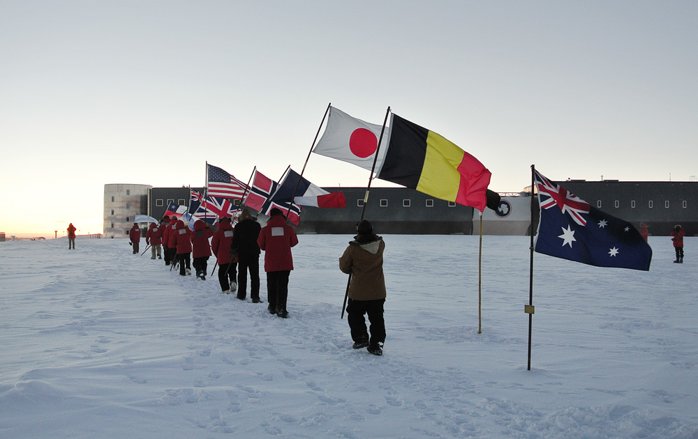 People march in a line carrying flags.