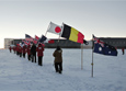 Members of the 2014 South Pole winter-over crew carry the flags from the 12 original signatory nations to the Antarctic Treaty inside the station.