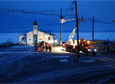 A lineman performs jumper repairs during a planned electrical outage at McMurdo Station near the Chapel of the Snows.