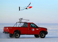 An unmanned aerial vehicle launches from the back of a pickup truck, which drives down a groomed runway near McMurdo Station.