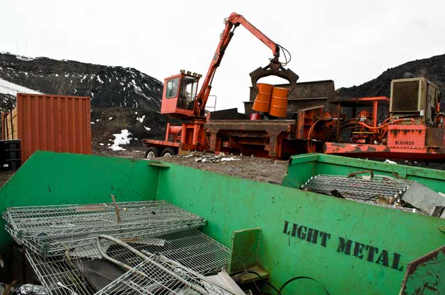 Machine lifts metal containers.