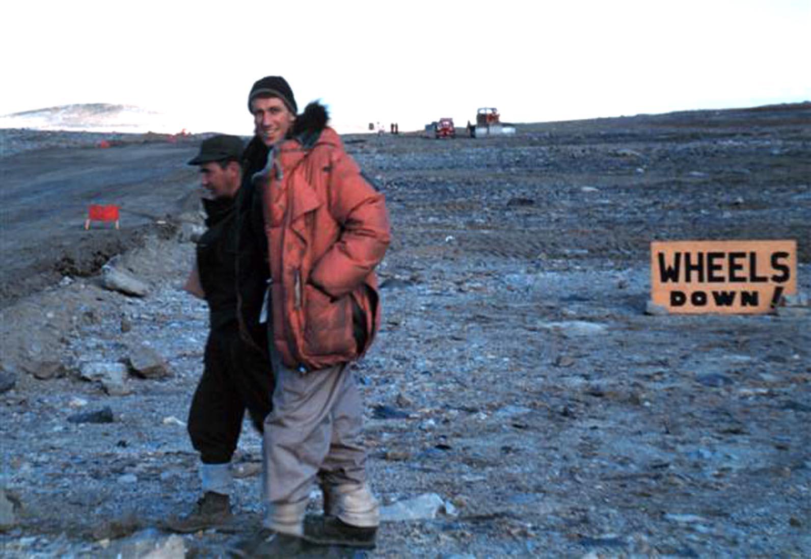 Two people walk across rocky ground.