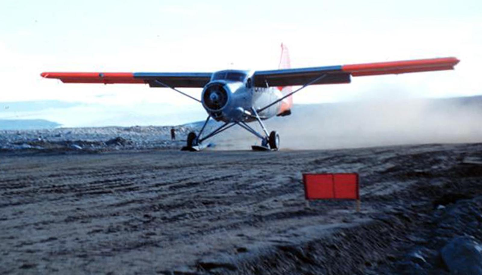 Old-style plane lands on dirt runway.