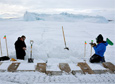 Mountaineers Ned Corkran and John Loomis examine a crack near an iceberg that is frozen in the sea ice close to Cape Evans, Ross Island.
