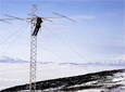 A man installs an antenna on a tower near McMurdo Station for an experiment during the 1963-64 field season. Photo by Wesley B. Harding.