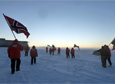Members of the 2015 South Pole Station winter-over crew remove the flags that encircle the ceremonial pole for the winter.