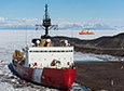 The Icebreaker USCGC Polar Star sits docked at McMurdo's ice pier, while the research vessel Nathaniel B. Palmer waits in the channel cut into the ice by the icebreaker.