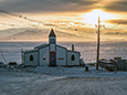 The sun sets behind McMurdo Station's Chapel of the Snows.