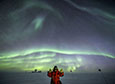 Robert Schwarz gives the thumbs up under bright auroras, with the South Pole telescope in the background.