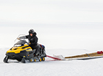 Field safety coordinator Philippe Wheelock drives a snowmobile across the ice shelf. Using the flags in tow, he's helping to mark the safe travel routes across the frozen landscape.