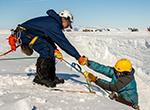 Search and Rescue supervisor John Loomis helps SAR team member Christina Bovinette out of a simulated crevasse during a training simulation.