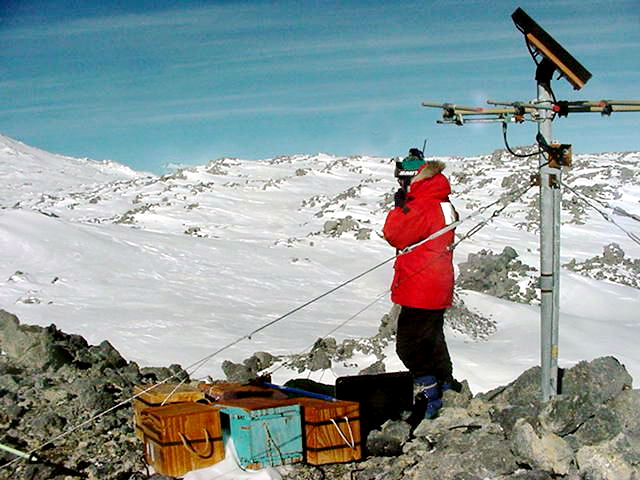 Scientist near seismometer on volcano.