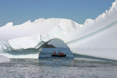 Small boat passes near iceberg.