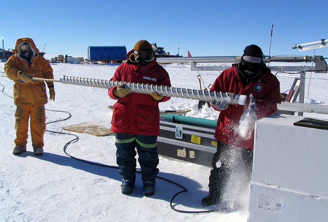 Scientists handle an ice core in Antarctica.