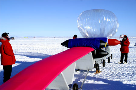 People inflate a balloon on ice.