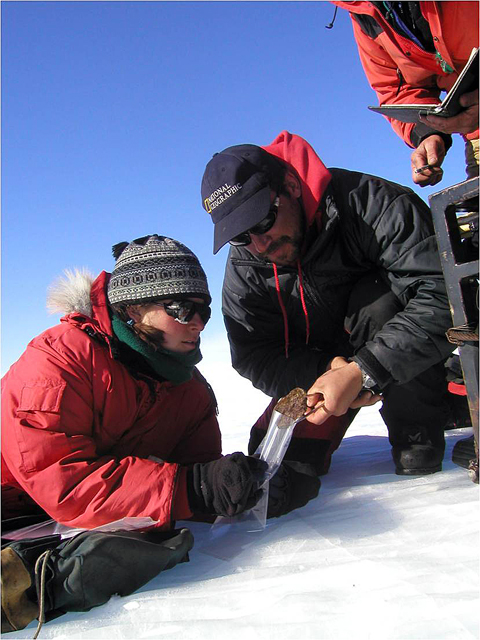 Field team members collect a space rock.