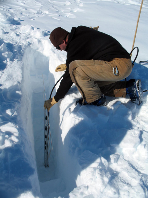 A scientist puts gear into the ice.