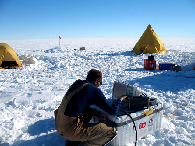 Scientist checks instrument in the field.